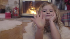 Little Girl Lays By Cozy Fireplace, Decorated For Christmas, She Waves To Camera Stock Footage