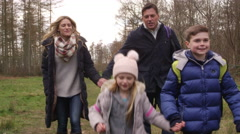 Family walking in woods towards tracking handheld camera, shot on R3D Stock Footage