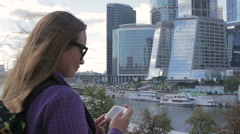 Young woman make a photo of high skyscraper using smartphone mobile cell phone Stock Footage