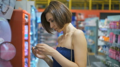 Young, beautiful woman in a supermarket chooses cosmetics Stock Footage