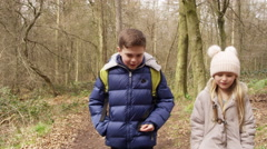 Two kids walking in woods towards tracking handheld camera, shot on R3D Stock Footage