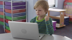 Small boy looking at laptop in classroom - 4K Stock Footage