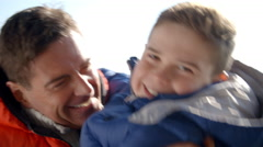 Father lifting son outdoors, both in warm clothing, close up Stock Footage