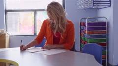Pre-school teacher writing grades - 4K Stock Footage