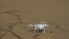 Quadrocopters takes off from the sand Stock Footage