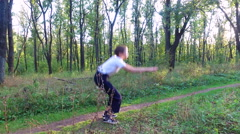Slim teen boy fulfills squats in the forest. Stock Footage