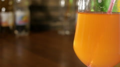 Straw for a cocktail in a glass, the bubbles in orange lemonade Stock Footage