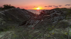 Sunset on the sea and dunes covered with logs. Timelapse Stock Footage