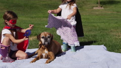 Young girls dressed as superheroes playing outside with their dog - 4K Stock Footage