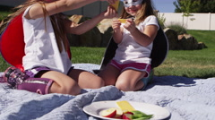 Young girls dressed as superheroes having picnic outside - 4K Stock Footage