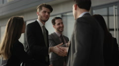 4K Business group meet & shake hands in crowded area of large modern office Stock Footage