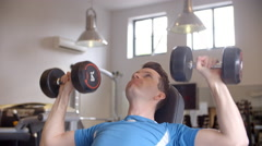 Man works out with dumbbells on a bench at a gym, front view Stock Footage