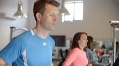 Man and two young women running on treadmills at a gym Stock Footage