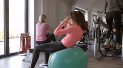 Woman doing crunches on a fitness ball at a gym, side view Stock Footage