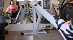 Woman on rowing machine at a gym in mirror, low angle Stock Footage