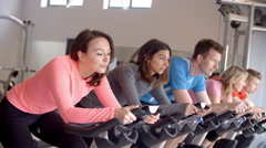 A row of people on exercise bikes in a spinning class at gym Stock Footage