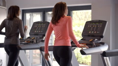 Two women exercise on running machines at a gym, back view Stock Footage