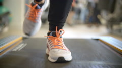 Close up of person's feet on a running machine, front view Stock Footage