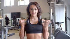 Woman doing bicep curls with dumbbells at a gym, front view, shot on R3D Stock Footage