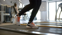 Woman exercising on running machine at a gym, low section Stock Footage