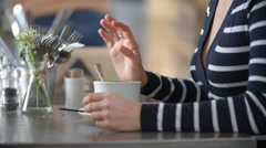 Close up of woman's hands stirring cup of coffee in a cafe Stock Footage