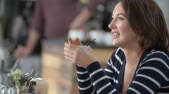 Woman sitting in a cafe, drinking with a straw, close up Stock Footage