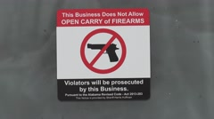 A posted signs bans the bringing of guns or firearms into a business. Stock Footage