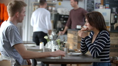 Adult couple talking at a table in a coffee shop woman using straw Stock Footage