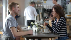 Adult couple talking at a table in a coffee shop, side view Stock Footage