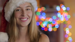 An attractive blond happy teenager laughing and wearing a Santa hat Stock Footage