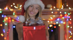A lovely young woman giving a wrapped Christmas gift and smiling Stock Footage