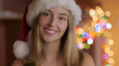 A smiling attractive young woman winks and smiles with a Santa hat Stock Footage