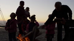 Family and friends roasting smores on the beach - 4K Stock Footage