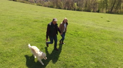 Aerial Shot Of Mature Couple And Dog On Walk In Countryside Stock Footage