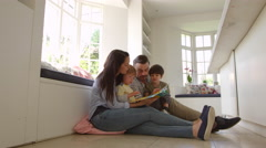 Family Sitting On Floor Reading Story At Home Shot On R3D Stock Footage