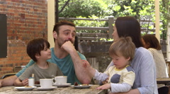 Family Sit At Outdoor Cafe Table Having Snack Shot On R3D Stock Footage