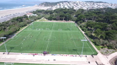 Aerial Drone Fly Over Green Soccer Field Ocean beach Stock Footage