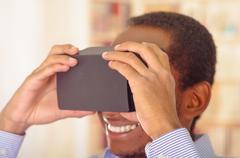 Man wearing blue shirt testing vitrual reality mobile device, holding glasses in Kuvituskuvat