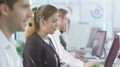 4K Portrait smiling customer service operator taking calls in busy call center. Arkistovideo