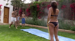 Family Having Fun On Water Slide In Garden Shot On R3D Stock Footage