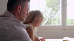Daughter With Father Drawing Picture At Table Shot On R3D Stock Footage