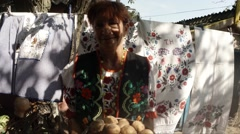 Ukrainian Woman in National Costume Holding a Pot With a Potato in the Shade of Stock Footage