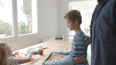 Parents And Children Baking Homemade Pizza In Oven Stock Footage