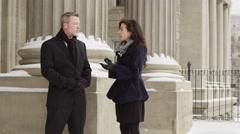 Female journalist interviews man on building steps - 4K Stock Footage