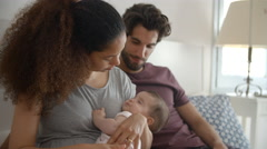 Parents Cuddling Baby Daughter In Bedroom At Home Stock Footage