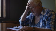 Troubled elderly man with head in hands looking sad and stressed Stock Footage