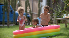 Children Having Fun In Garden Paddling Pool Stock Footage