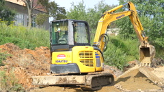 Yellow excavator working on a construction site Stock Footage