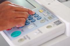 Closeup fingers pressing display buttons on photocopier Stock Photos