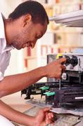 Man leaning over open photocopier during maintenance repairs using handheld tool Stock Photos